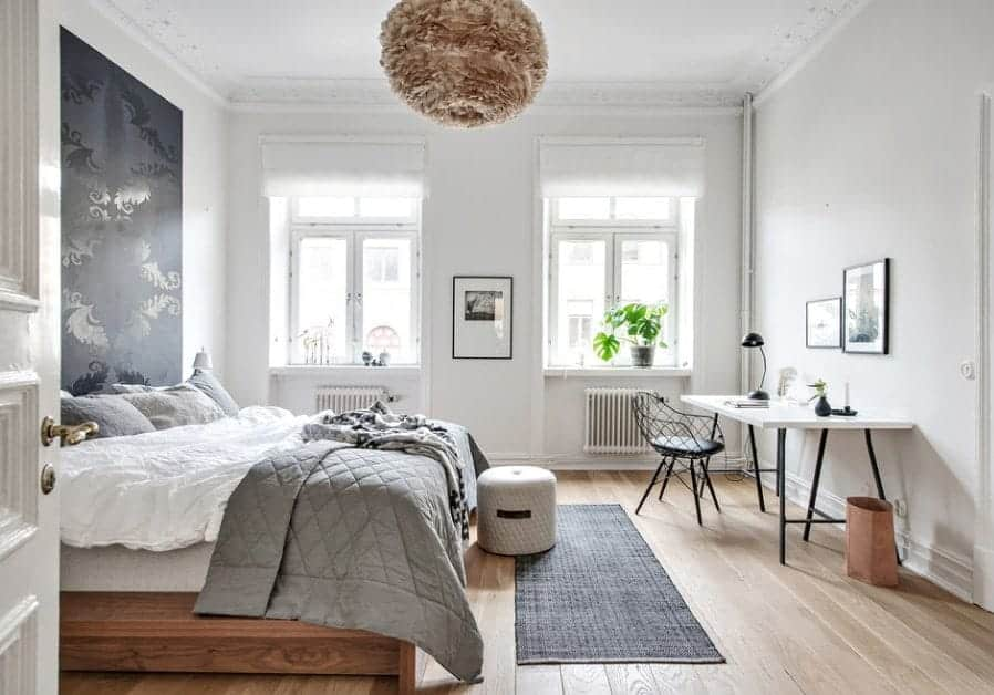 This Scandinavian-Style primary bedroom features a stylish wall design and a study desk on the side. The room also features hardwood flooring.