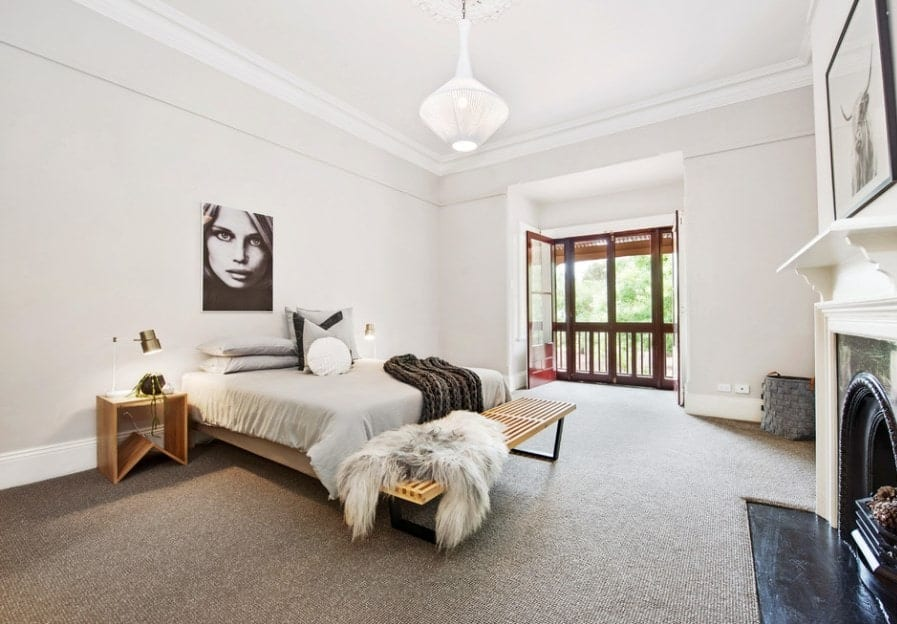 Large Scandinavian-Style primary bedroom with white walls and gray carpet flooring along with a classy fireplace.
