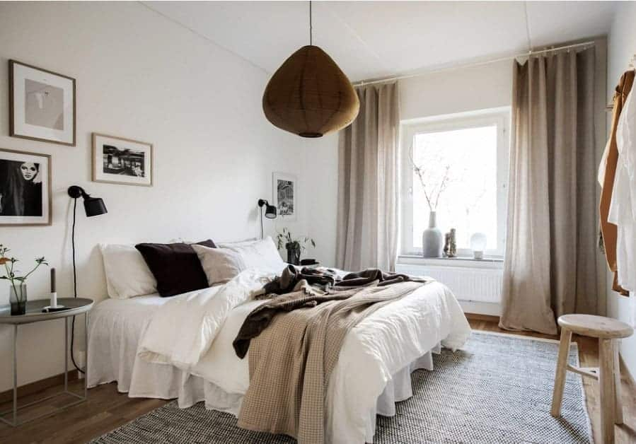 A Scandinavian-Style primary bedroom featuring white walls with multiple eye-catching wall decors on frames. The pendant lighting is very attractive as well.