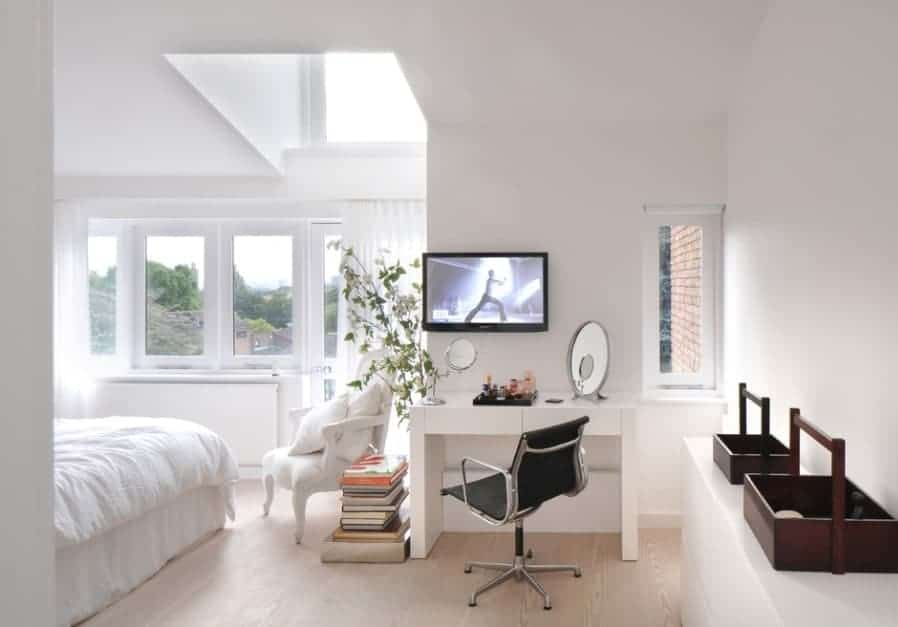 A classy Scandinavian-Style primary bedroom featuring white walls and ceiling along with white window curtains and a makeup desk with a TV on the wall.
