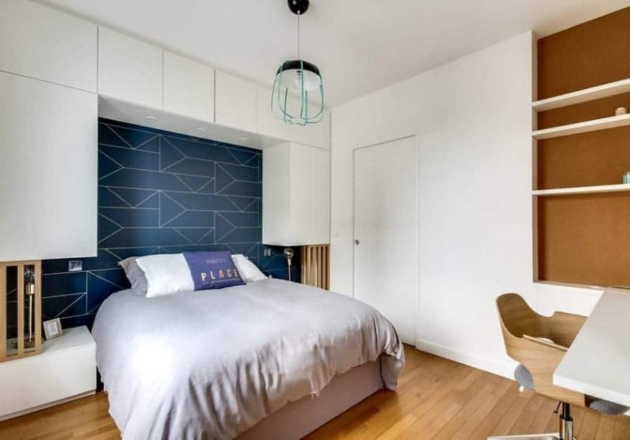 A modish Scandinavian-Style primary bedroom with a stylish wall and a small study desk with multiple shelves on the wall.