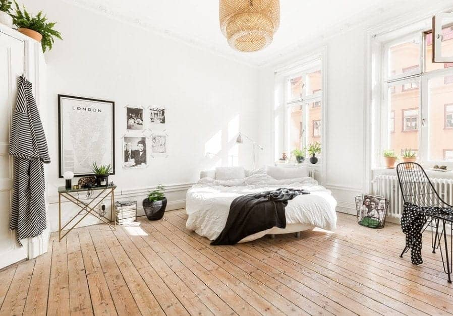 Large Scandinavian-Style primary bedroom featuring white walls and ceiling and hardwood flooring. The bed looks very romantic.