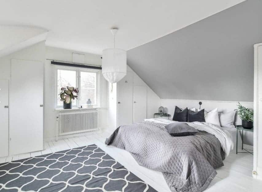 This Scandinavian-Style primary bedroom boasts white walls and ceiling along with white hardwood flooring topped by a stylish rug.