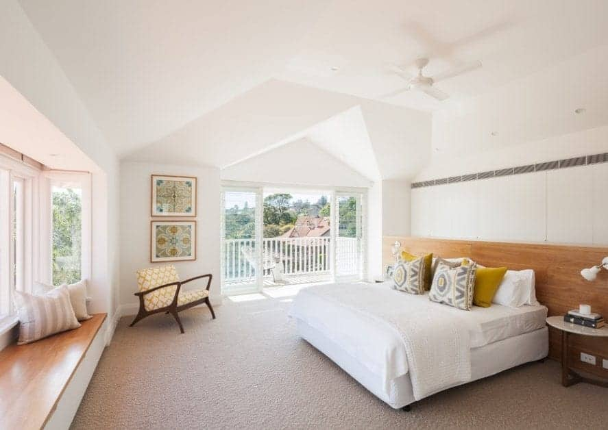 Large Scandinavian-Style primary bedroom featuring a stylish ceiling and classy carpet flooring along with private balcony space.