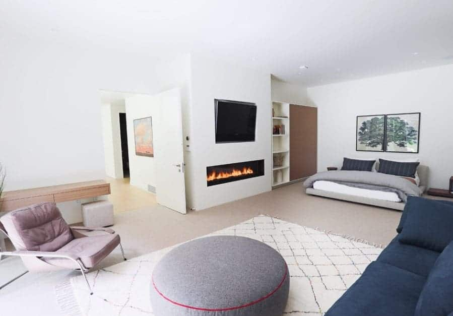 A modish Scandinavian-Style primary bedroom with its own living space offering cozy seats and a fireplace.