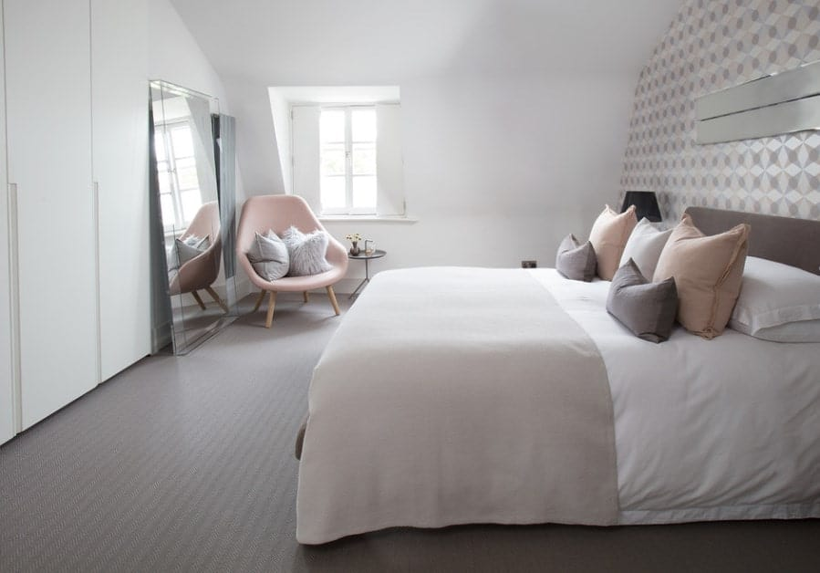 Classy Scandinavian-Style primary bedroom featuring gray rug flooring and a stylish wall. There's a cute pink chair on the corner near the window.