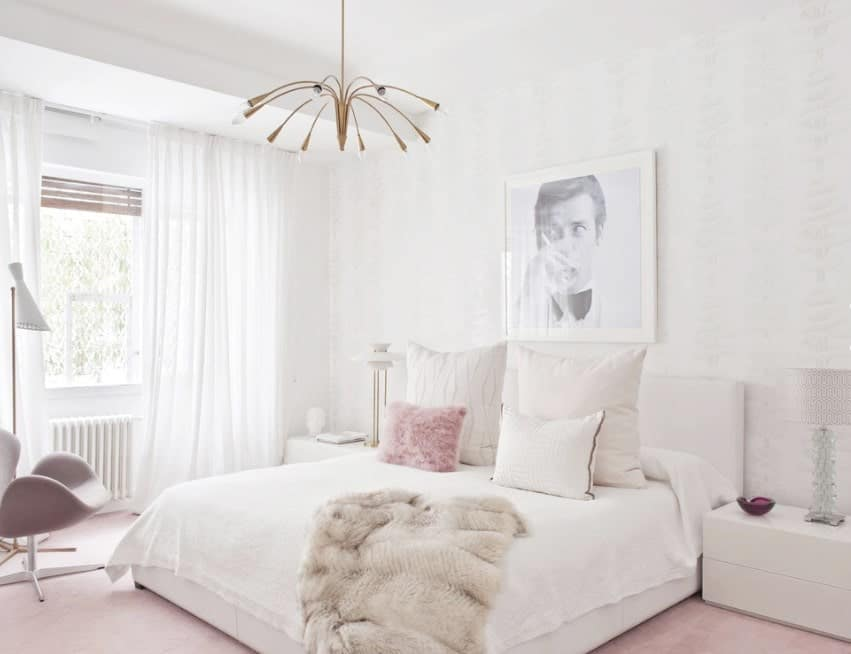 A chic Scandinavian-style primary bedroom with pink carpet flooring and white walls that match the bed and side tables perfectly. The white window curtains look very lovely as well.