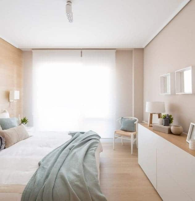 Small Scandinavian-Style primary bedroom with lovely window curtains and beige walls that fit perfectly well with the room's style.