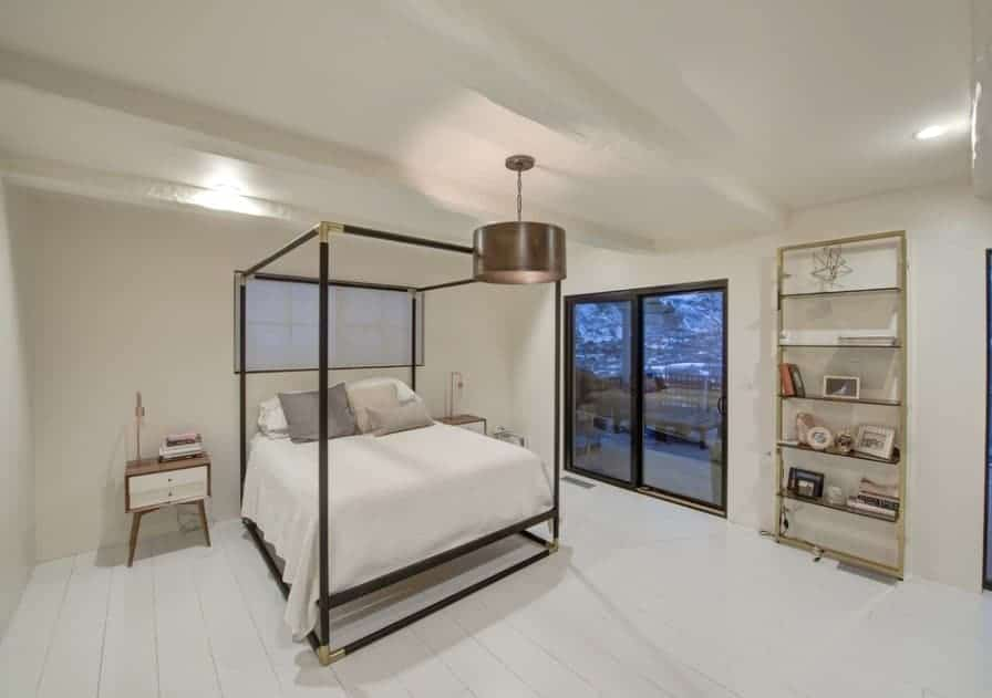 A modish Scandinavian-Style primary bedroom featuring white hardwood floors and stylish side tables along with shelving on the side.