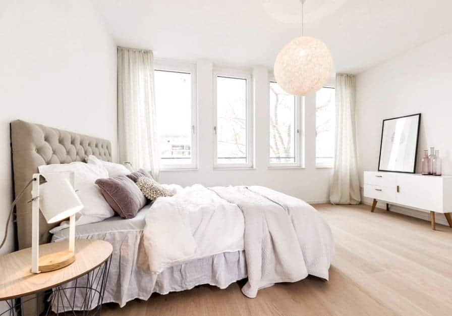 White Scandinavian-Style primary bedroom with a stunning bed and classy white window curtains matching the white walls. The pendant light is just so glamorous.