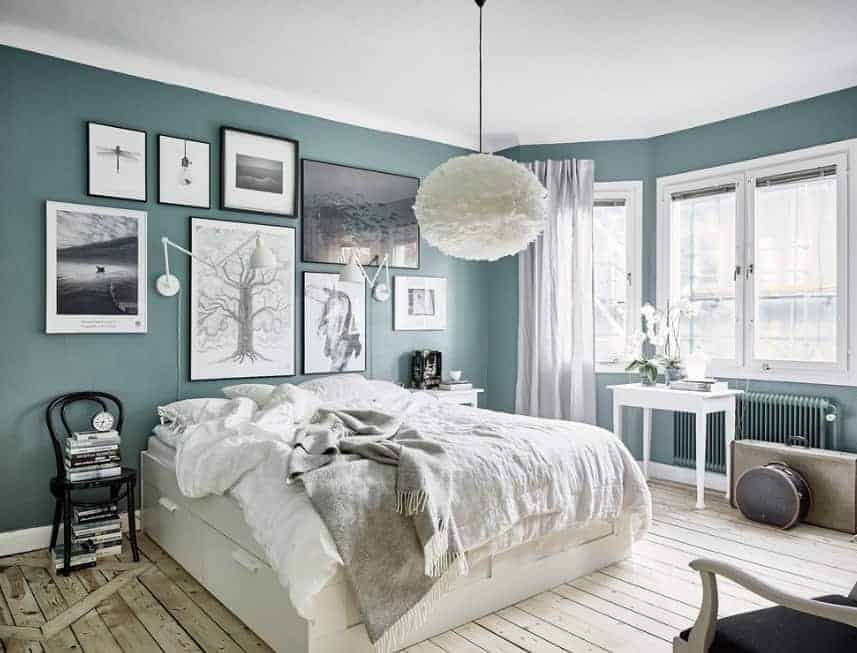A very attractive Scandinavian-Style primary bedroom with green walls decorated with multiple artistic wall decors. The ceiling lighting looks so charming as well.