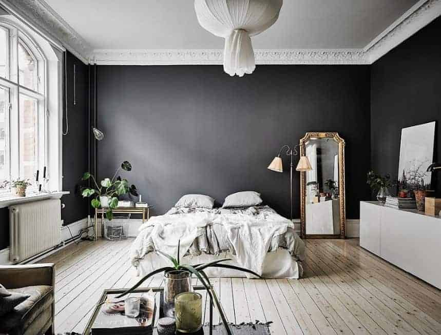 This Scandinavian-Style primary bedroom boasts elegant black walls surrounding the room. The hardwood flooring adds charm to the area. The ceiling looks stunning as well.