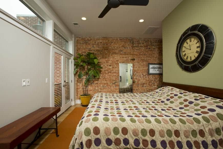 The colorful patterned sheet of the bed is paired with a low wooden headboard that is topped with an antique bulky wall-mounted clock on a light green wall. This is contrasted by the adjacent red brick wall with a potted plant in the corner.