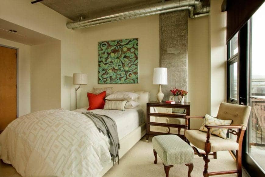 This charming master bedroom is a lovely fusion of traditional-style and industrial-style. It has a traditional bed that complements the beige carpeted flooring and beige walls. This is accented with exposed pipes and vents of the concrete ceiling.
