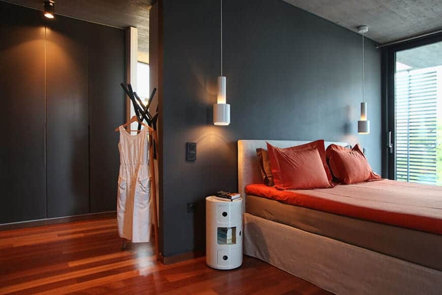 The gray concrete ceiling hangs a couple of modern white pendant lights on either side of the bed. these lights stand out against the black wall of the bed together with the white barrel-like bedside tables that contrast the redwood flooring.