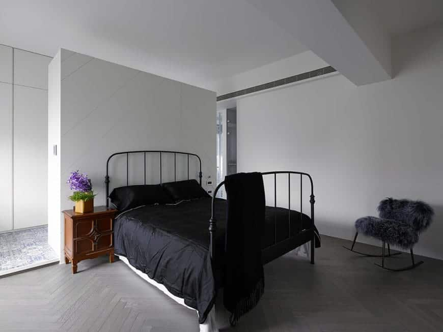 The black wrought iron bed frame matches with the black sheets that is complemented by the gray concrete flooring with a herring bone pattern to it contrasted by smooth white walls and ceiling.