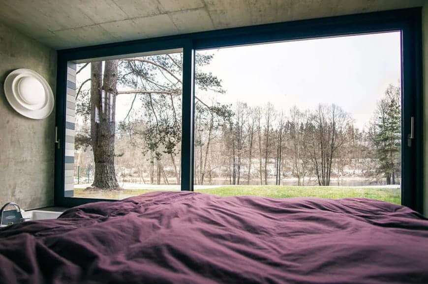 A whole wall of this master bedroom is made of wide sliding glass doors that gives an unobstructed view of the surrounding landscape scenery of trees and grassy lawn. This serves as a nice background for the concrete gray walls and ceiling.