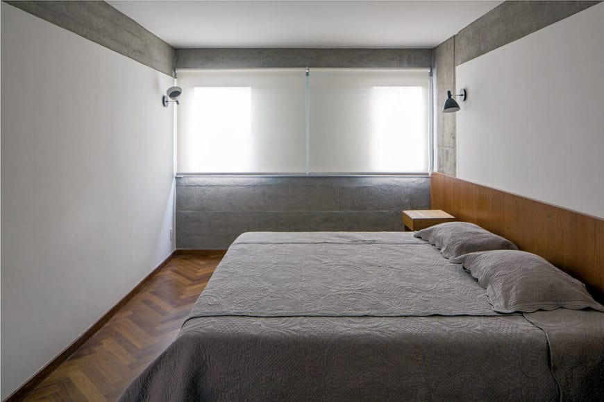 The white walls and ceiling are accented with sections of gray concrete that matches with the gray sheets of the bed that has a wooden headboard extending to the bedside tables that matches with the hardwood flooring.