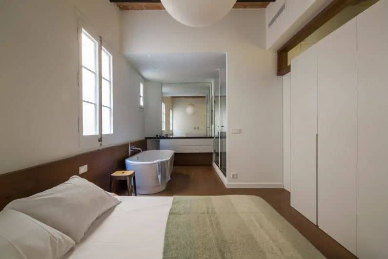 This is an industrial-style bedroom beside the bathroom on the same hardwood flooring that contrasts the white cushion with no bed frame. This hardwood flooring extends to a low wainscoting and matches with the wooden ceiling with exposed wooden beams.
