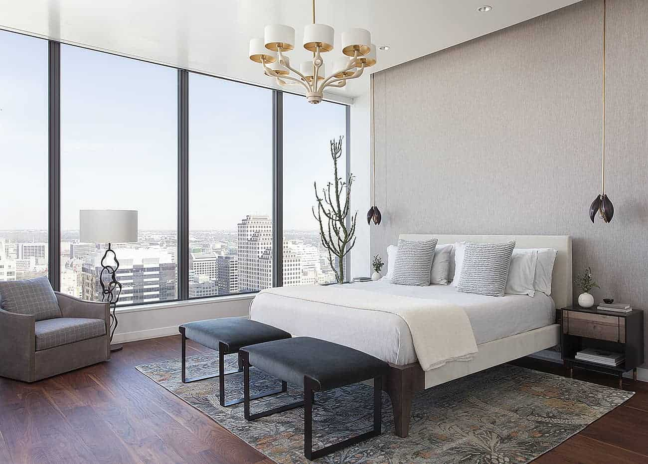 The dark hardwood flooring of this master bedroom is brightened by the large glass walls on the right side of the bed that has a light gray headboard against a gray concrete wall accented with a pair of flower-like pendant lights.
