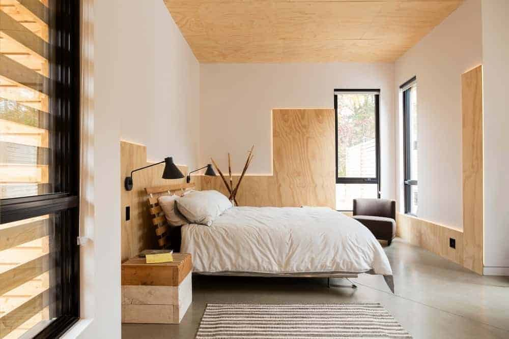 The ceiling of this master bedroom is made of bare plywood that matches with the wooden accents of the white walls trimmed with back lighting to emphasize the lines. This is complemented by an industrial-style concrete flooring that goes well with the wooden bed flanked with repurposed wooden palette boxes.
