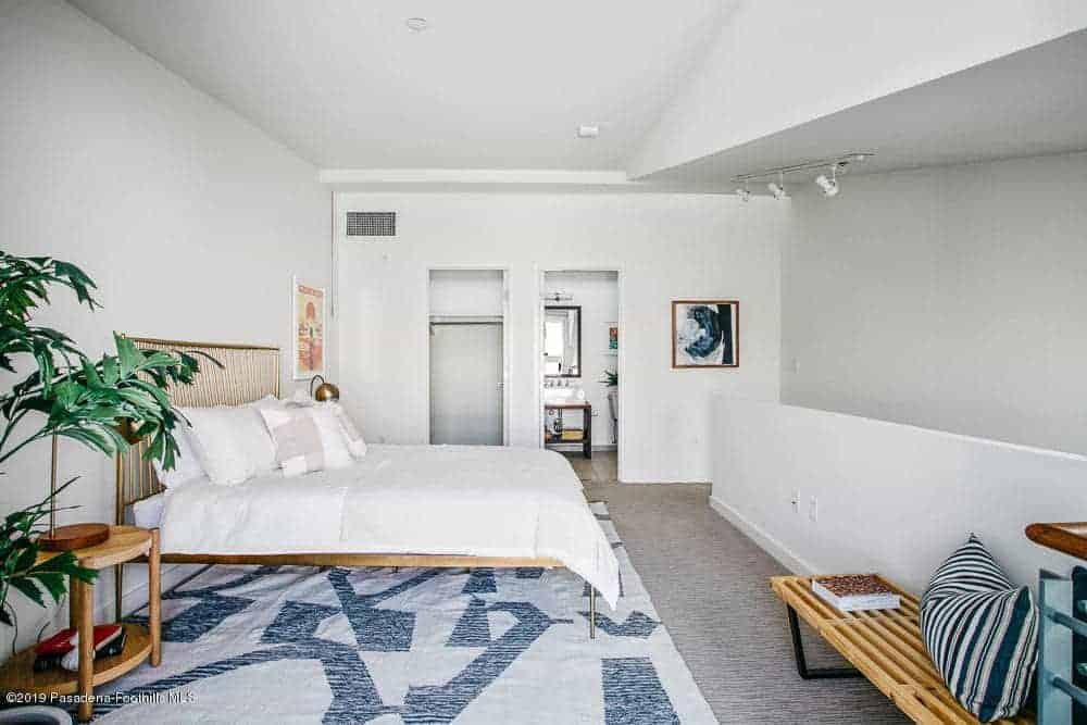 This master bedroom has white walls and white ceiling that matches the white sheets of the bed that has an industrial-style brass frame that pairs well with the brass table lamps on the bedside tables flanking the bed over a gray carpeted flooring.
