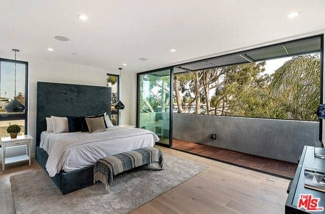This industrial-style bedroom has a large wall that opens with sliding glass doors to a balcony with concrete walls that match with the gray area rug underneath the green bed with a green velvet headboard that stands out against the white wall flanked with thin windows.
