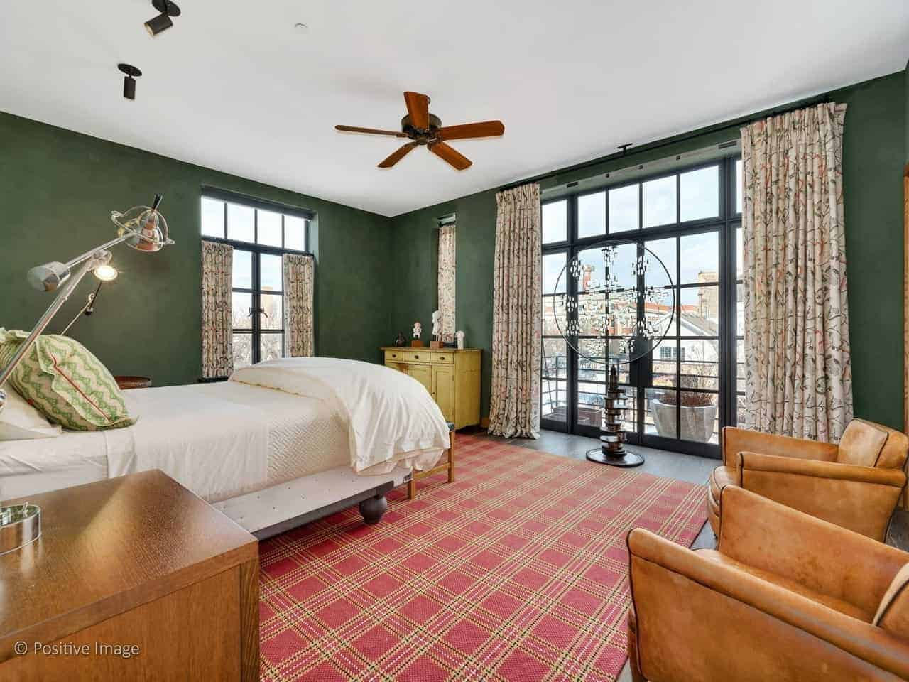 This industrial-style master bedroom has dark green walls that are contrasted by the large French window and French glass doors. These are paired with floral curtains that pairs with the red plaid area rug to bring a dash of color to the bedroom.