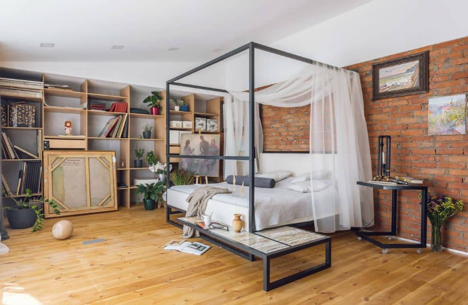 The highlight of this industrial-style master bedroom is the large customized four-poster bed that has gray frames with a built-in chair and shelf by the foot paired well with a wheeled bedside table that can double as a small desk. This setup has a nice background of red brick walls and hardwood flooring.
