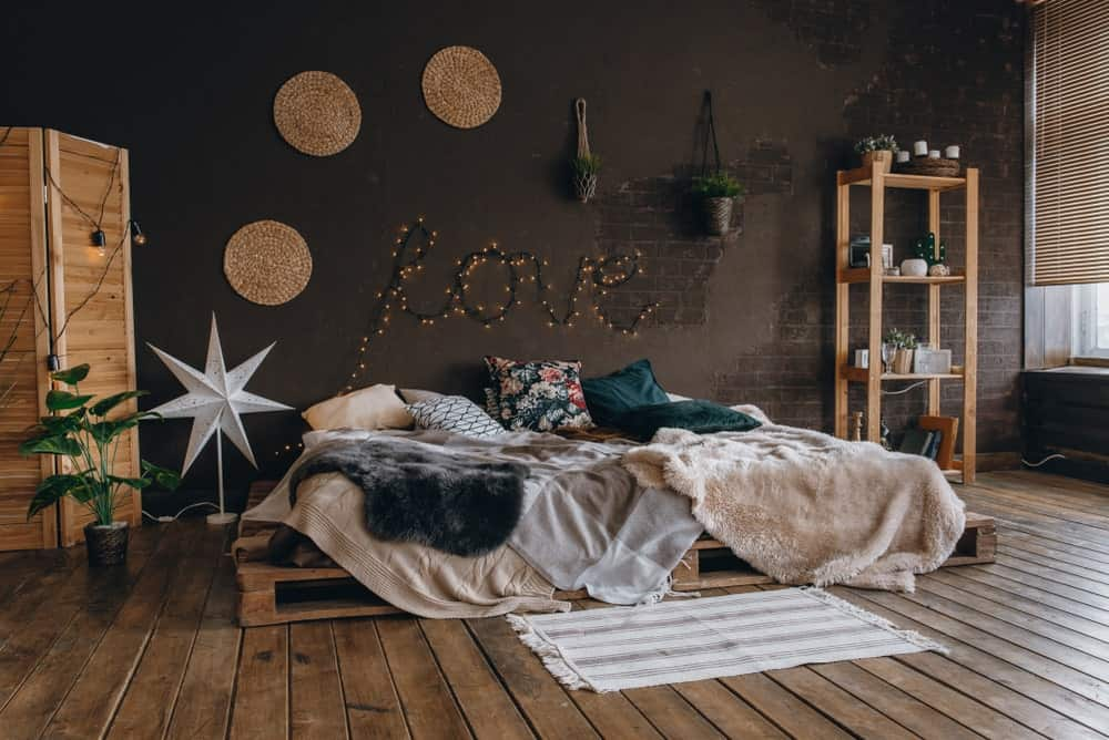 This industrial-style master bedroom has a romantic vibe to it with a platform bed frame made of pallet crates that blend with the distressed hardwood flooring and complements the wooden structures of the room that stand out against the dark gray wall.