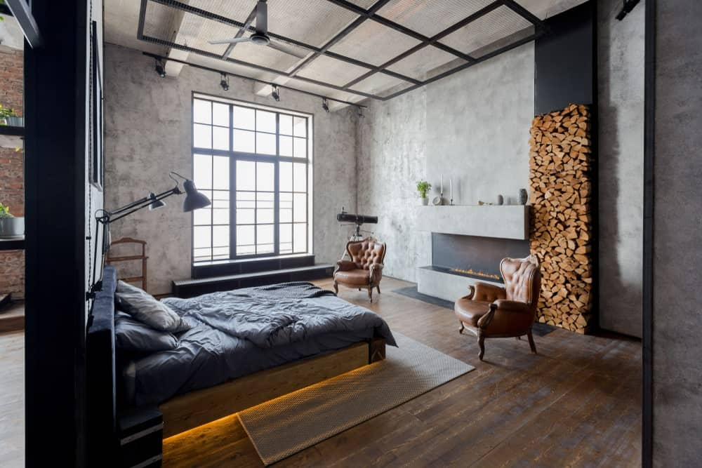 This industrial-style bedroom has a warm fireplace embedded into a gray concrete wall with a firewood storage beside it. The wooden traditional bed across from it has a back lighting underneath that gives the hardwood flooring and woven area rug an ethereal yellow glow.