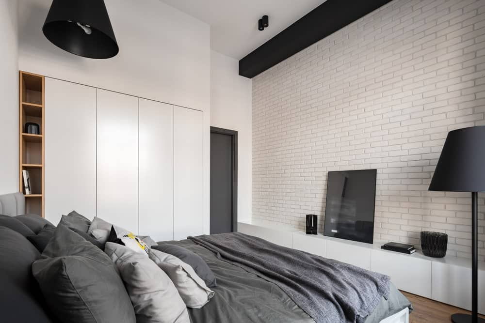 The dark gray sheets and pillows of the traditional bed stands out against this predominantly white master bedroom that has white brick walls, white cabinets embedded into the white walls and a white ceiling that is contrasted by the black pendant light and beam.