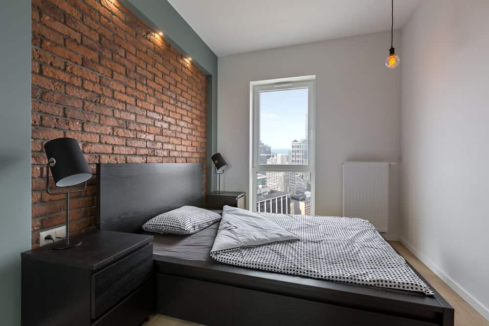 The simplicity of this industrial-style bedroom brings focus to its red brick wall that complements the black wooden headboard of the platform-style black wooden bed. This matches with the black wooden bedside drawers and its table lamps.
