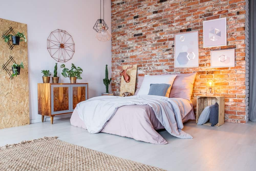 This charming industrial-style bedroom has a chic quality to its aesthetic of pink bed sheets, red brick wall and a palette crate bedside table that also acts as pillow storage. The red brick wall is adorned with white artworks that match the flooring.