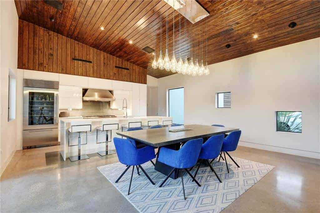 The wooden shed ceiling has a dark brown hue to it that is augmented by the warm yellow lights of the recessed lights and the pendant lights hanging over the wooden dining table surrounded by blue velvet armchairs that stand out against the industrial-style flooring.