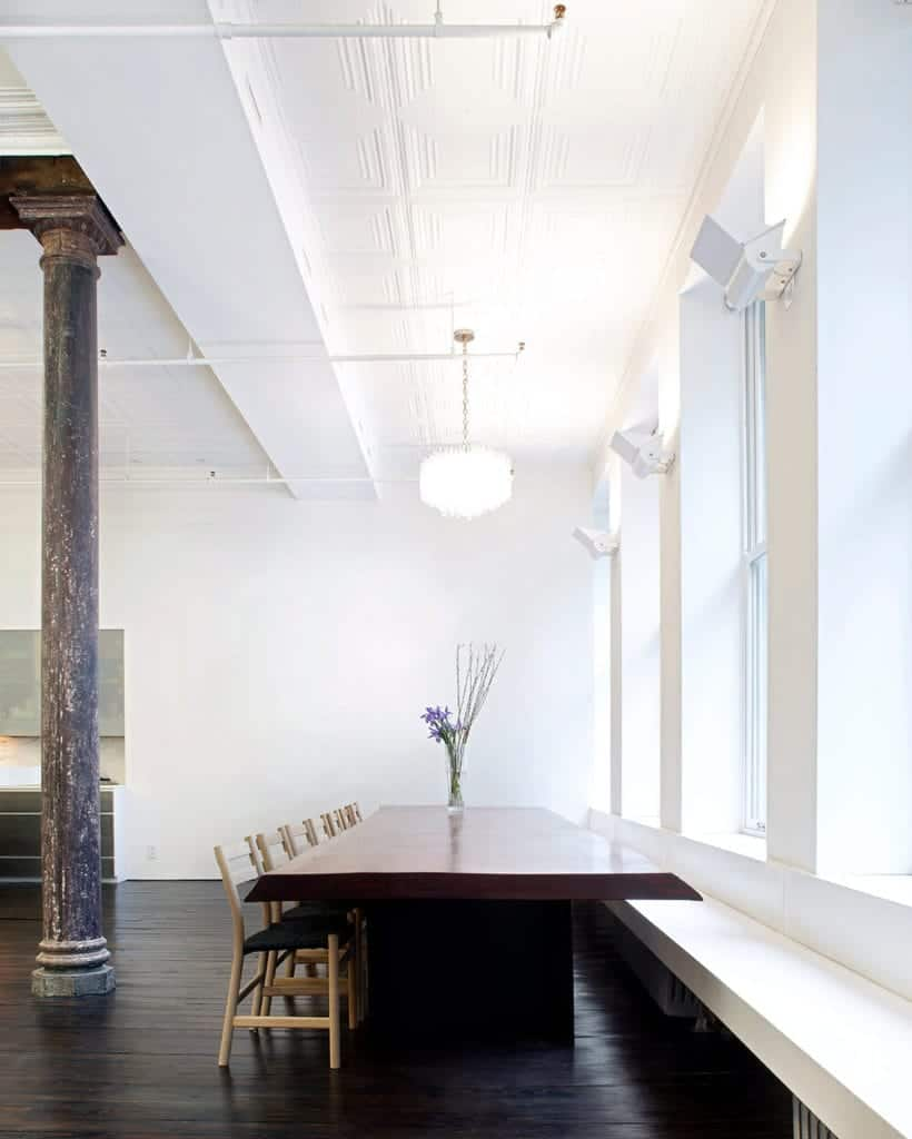 The large wooden dining table is paired with a built-in long bench on one side and a row of wooden chairs on the other side, These are all over a dark hardwood flooring and a high ceiling with exposed pipes.