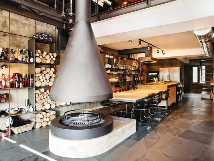 This dining area is in the middle of a large circular fireplace and the kitchen island all on a gray industrial flooring and a white ceiling that has exposed stainless steel ducts and vents. The dining area has a wooden table paired with modern chairs.
