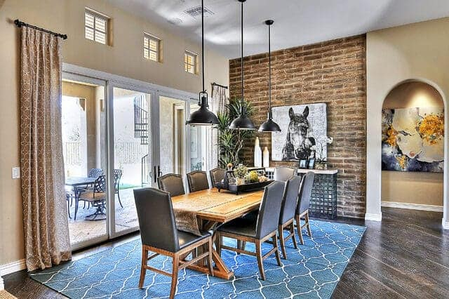 This dining room has an adobe brick wall with a dark gray hue that matches the hardwood flooring covered by a green patterned area rug underneath the wooden dining table paired with gray leather cushioned chairs.