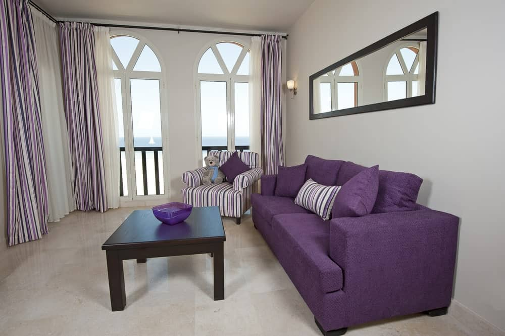 Airy living room with tiled flooring and arched windows covered in striped draperies that complement the armchair and accent pillow. It includes a purple sofa and dark wood coffee table topped with a decorative bowl.