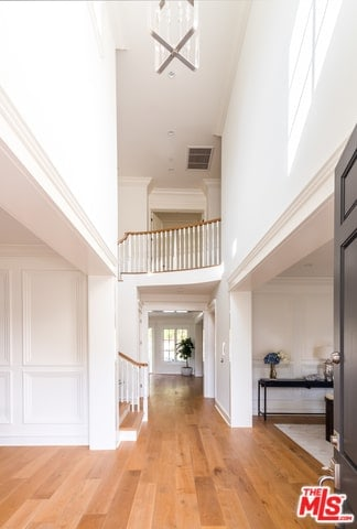 This is a high-ceiling and bright foyer with a Farmhouse-style aesthetic. It has a hardwood flooring that is contrasted by the white walls and the white ceiling that are all brightened by the natural lights coming in from the front door.