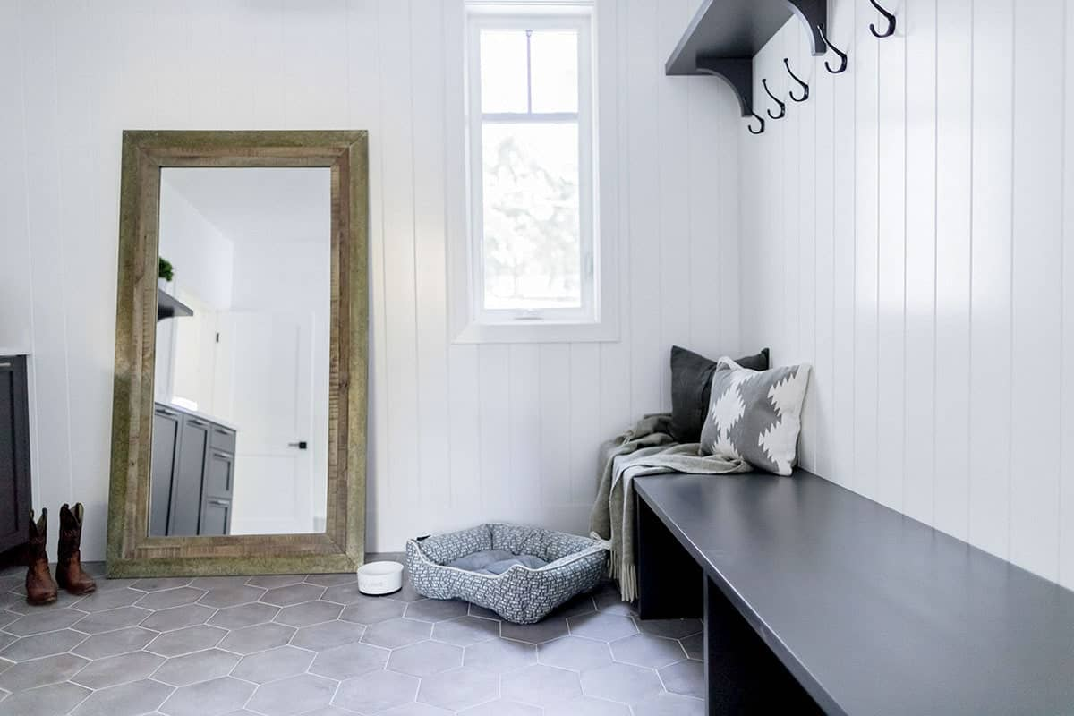 This charming Farmhouse-style foyer has a mudroom upon entry of the main door. It has a long wooden black bench with space underneath for the shoes, dark hooks that stand out against the white plank wall and a black wooden shelf above it.