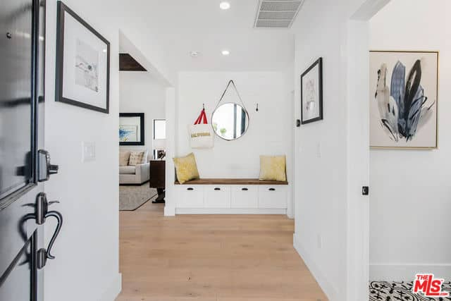 As you enter this bright Farmhouse-style foyer, you will see a a sitting area for the waiting guests. It has a built-in bench with a wooden top embedded into the white wall. This bench has storage areas at the bottom for the shoes and hooks on its wall for the coats, hats and bags.