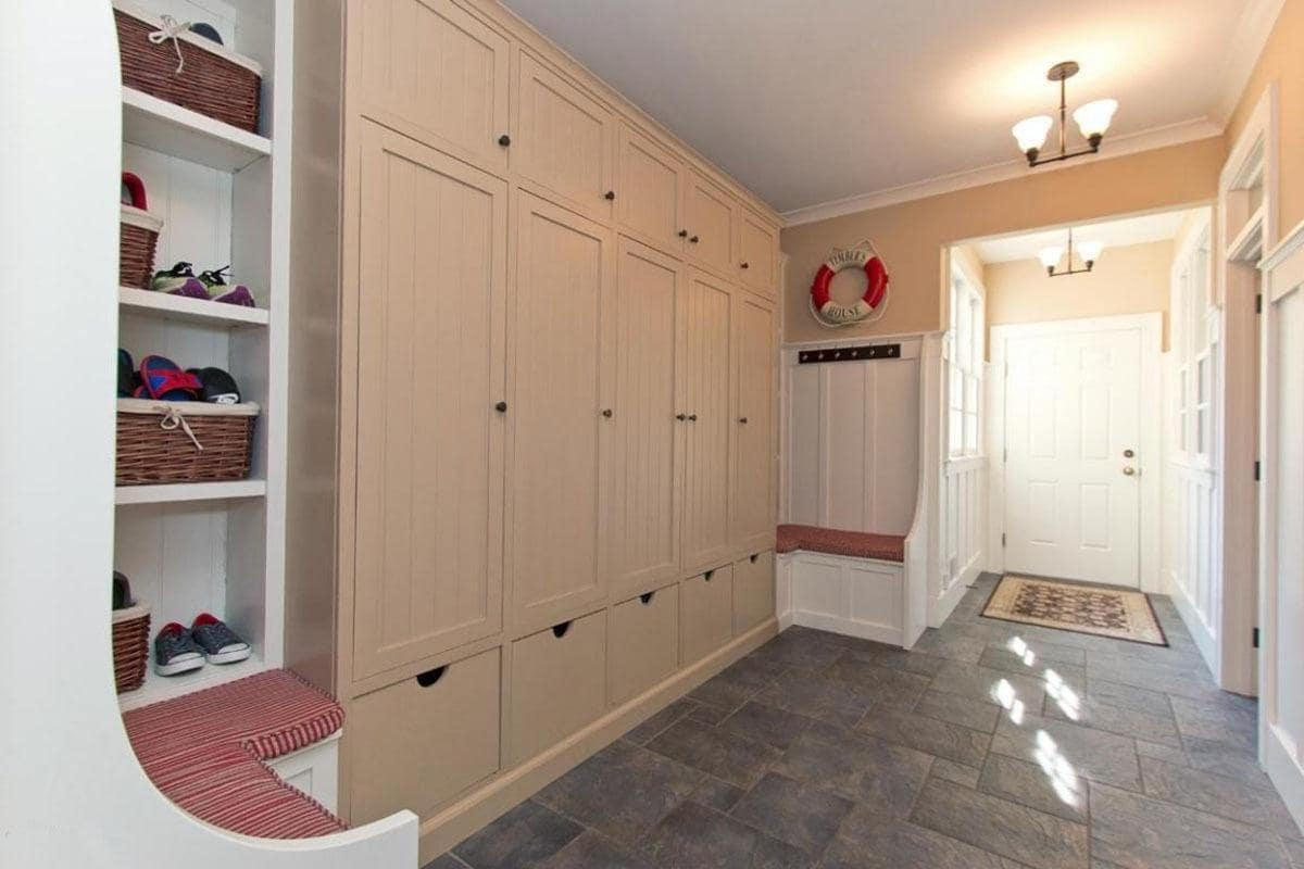 Upon entry of the white wooden door that is topped with a bright yellow lighting, you will be welcomed into this charming mudroom that has a dark gray stone textured flooring that contrasts the white wooden structures flanking the large brown wooden cabinet.