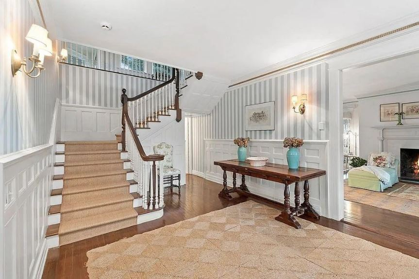 The dark hardwood flooring of this elegant foyer is mostly covered by a brown woven area rug that matches with the carpeting of the stairs. These are augmented by the white wainscoting contrasted by the dark wooden console table bearing flower vases.