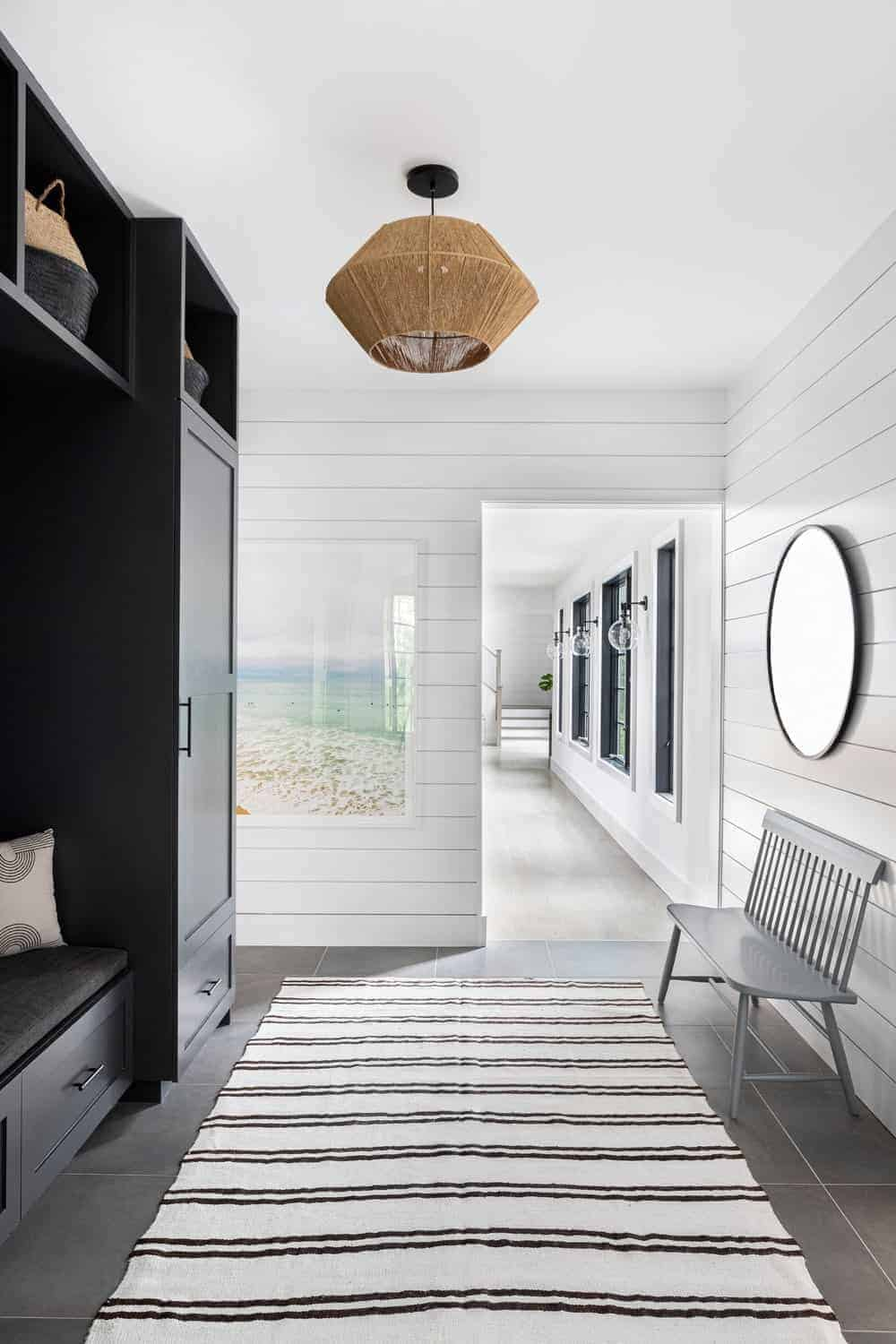 The white ceiling of this Farmhouse-style foyer is adorned with a pendant light that has a woven basket hood that provides a rustic element to the dark wooden mudroom on the left side with a cushioned seat. Opposite this is a light gray wooden bench against the white plank wall.