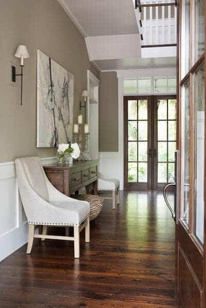 The dark wooden main that has glass panels on it matches with the dark hardwood flooring of the Farmhouse-style foyer that has a comfortable cushioned chair on the side for the waiting guests.