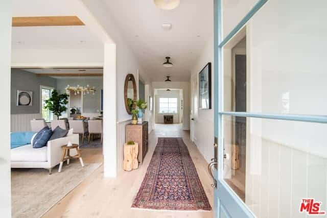 The charming main door of this home has a light blue hue and has glass panels on it that brings in natural lighting to the light hardwood flooring balanced by a colorful patterned area rug. Further in, the white hallway is adorned with wooden decors and a wooden cabinet topped with a circular mirror.