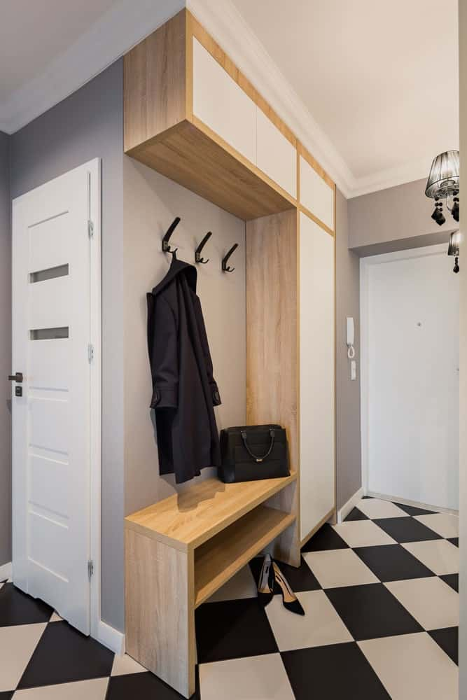 This charming foyer has a black and white checkered flooring that complements the large wooden mudroom that has a wooden bench, black hooks for the coats and built-in cabinets and shelves for storage. This structure goes well with the gray walls.