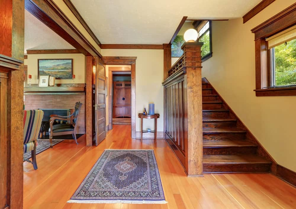 This Farmhouse-style foyer has a good view of the wooden staircase that has a wooden wall on the left side that complements the hardwood flooring that is topped with a colorful patterned area rug before the entry way of the living room on the left side.