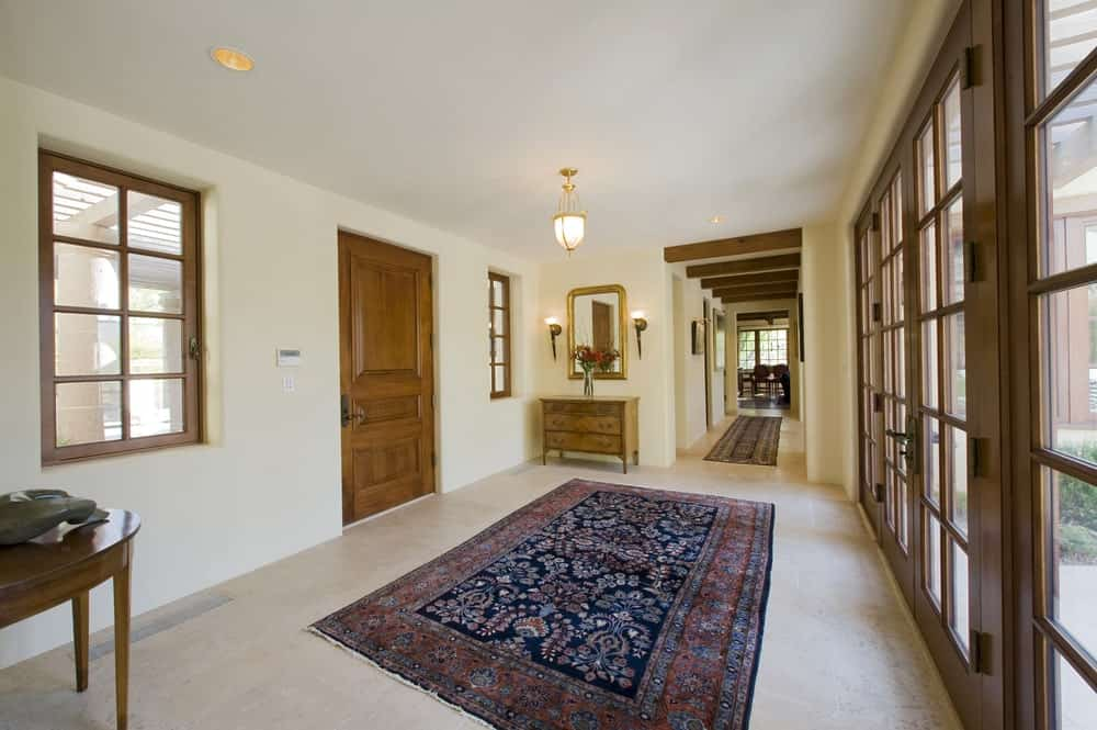 The wide main doors are filled with glass panels on it in a French-style. This brings in an abundance of natural lighting to the foyer that has a colorful patterned area rug in the middle of the beige floor topped with a yellow pendant light matching with the wall lamps above the dresser.